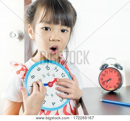 Little asian girl holding toy clock for school time