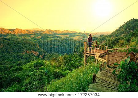 Woman raising arms standing on the old wood balcony terrace with mountain view in the morning during sunrise at Baan Ja Bo Mae Hong Son Thailand
