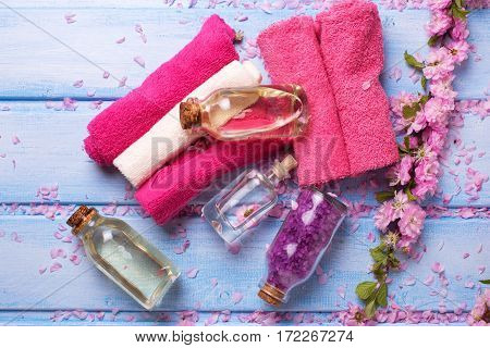 Bottles with spa products flowers and towels on blue wooden background. Selective focus. Top view.