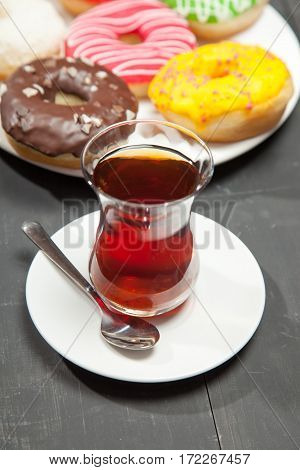 Donut. Sweet food and cup of coffee, tea drink. Breakfast, dessert with cake, snack. Brown wooden table. Bakery, sugar doughnut. Tasty espresso black hot morning beverage.