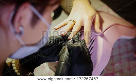 Polishing nails - female get professional manicure in beauty shop - top view, close up