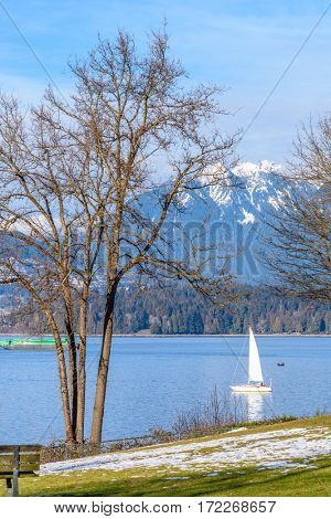 View on beautiful Vancouver park and harbour over snow mountains.