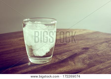 Glass Of Fresh Mineral Water With Ice Cubes On Wood Table With Vintage Color. Empty Ready For Your P