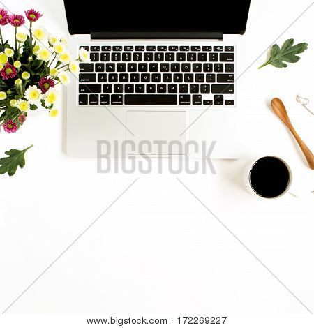 Top view home office table desk. Workspace with laptop wildflowers bouquet coffee cup feminine accessories and office stuff. Flat lay.