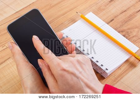 Hand Of Woman Using Mobile Phone, Notepad For Writing Notes