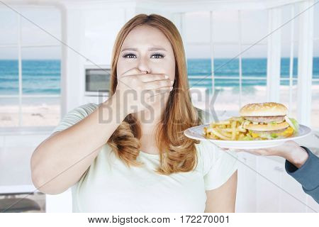 Portrait of beautiful woman refusing french fries and hamburger while closed her mouth
