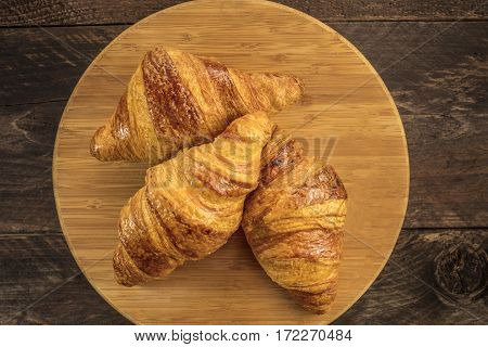 An overhead photo of three crunchy croissants on a wooden board with a place for text