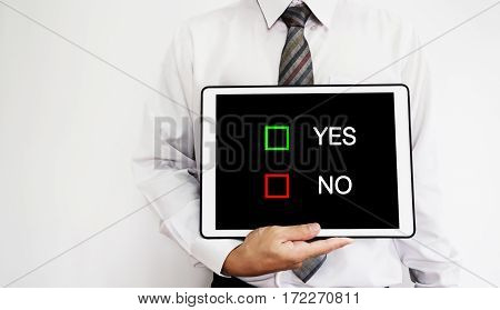 Business employee holding digital tablet with YES or NO choices selection on screen