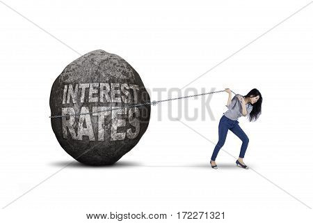 Image of young businesswoman dragging big stone with text of interest rates isolated on white background