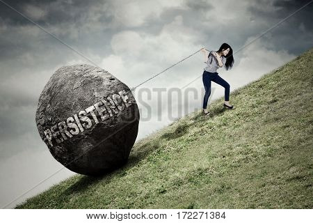 Female entrepreneur climbing on the hill while pulling big stone with persistence word