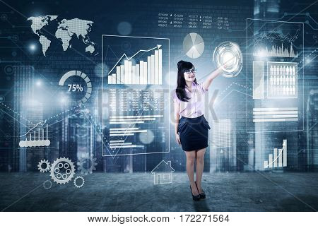 Picture of a young businesswoman pressing virtual icon with financial graph on the digital screen