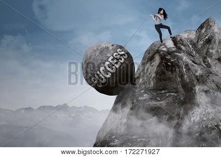 Young businesswoman is pulling big rock with success word while climbing on the mountain