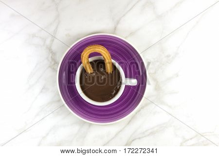 Churros, traditional Spanish, especially Madrid, dessert, particularly for Sunday breakfast, in a cup of hot chocolate, shot from above on a white marble texture with a place for text