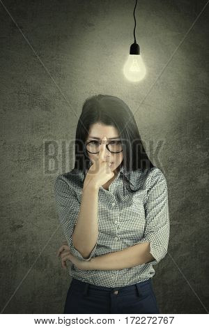 Portrait of young businesswoman thinking about something with a light bulb above head