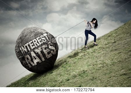 Young businesswoman pulling big stone with text of interest rates while climbing on the hill