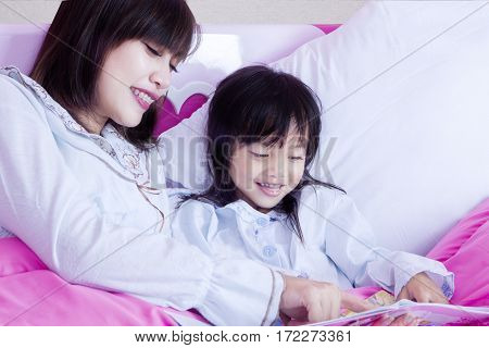 Happy little girl and her mother lying on the bedroom while reading a storybook shot at home