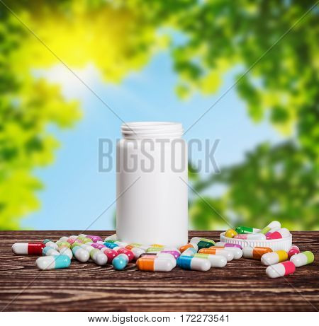 pills of different colors and a bottle of medicine against the background of nature