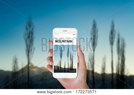 woman using her smart phone for searching the travel information of beautiful Himalayan landscape at the sunrise time Ladakh India. Traveling concept Himalayan range blurry background.