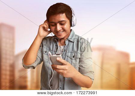 Asian man enjoy listening music wearing headphones
