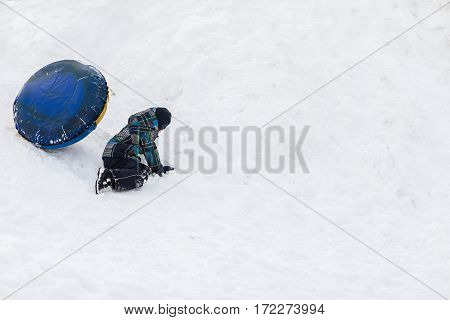 Funny child falling from the snowy mountains with tubing in the winter.
