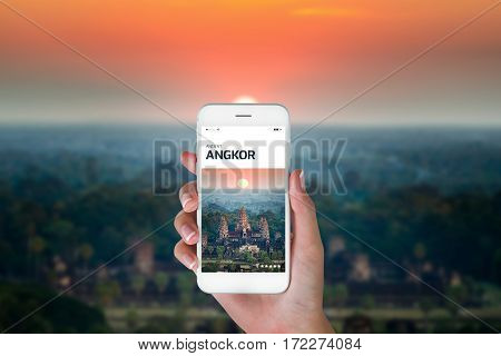 Woman using her smart phone for searching the travel information of aerial view Angkor Wat at sunrise time Siem Reap Cambodia. Traveling concept aerial view Angkor Wat blurry background.