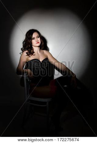 Sexy girl in lacy lingerie and corset, sitting on chair posing in the studio a dark background.