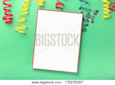 Blank card with colorful streamers and confetti on a bright background. Flat lay