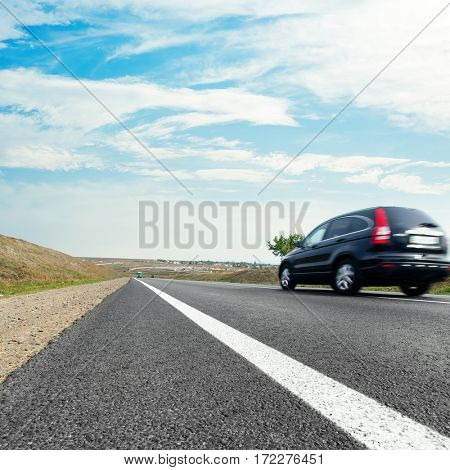 black car in motion on asphalt road and blue sky with clouds