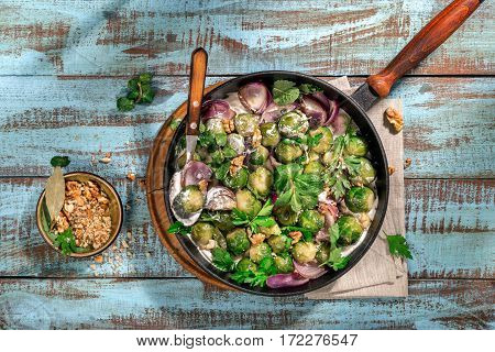 Roasted sprouts in a cast iron frying pan on a wooden table top view. Healthy food