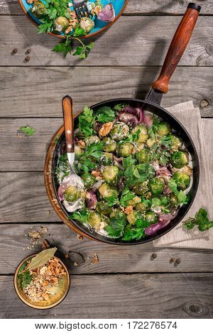Healthy food. Roasted sprouts in the greek yogurt with nuts onions parsley and mint in a cast iron frying pan on a wooden table top view