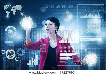 Picture of female entrepreneur working with virtual screen while pressing digital button and financial graph