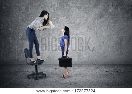 Picture of female leader screaming to her female staff with a megaphone while standing on the chair