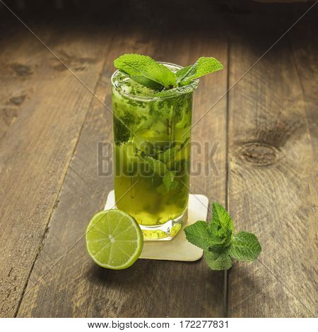 A square photo of a mojito cocktail with mint leaves and a wedge of lime on a dark wooden background with copyspace