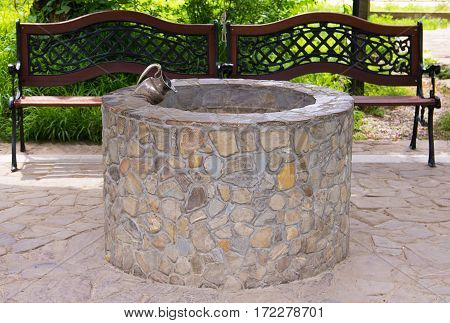 stone well with the figure of a pitcher is in a quiet alcove next to benches with curved wrought back