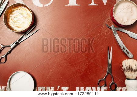 Barber tools frame on red background flat lay. Top view on gules table with scissors, razor and hair wax, free space for text or advertisement. Barbershop, manhood, beauty concept