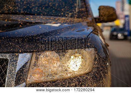 dirty black SUV Headlight close-up, focus on the spotlight