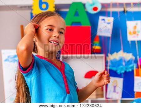 Child portrait in kindergarten. Small student girl painting in art class. Little girl in primary school. Craft group childrens drawings background interior.