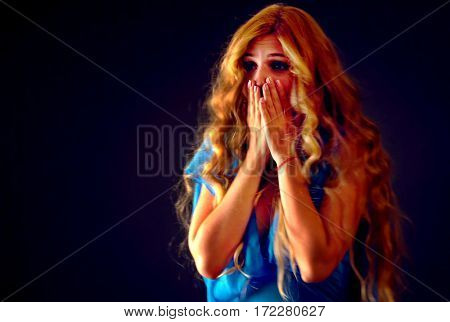 Frightened woman screaming with fear indoor at halloween night. Horror. Worried girl with tousled hair worried bawl and l covers her mouth with her hands black background.