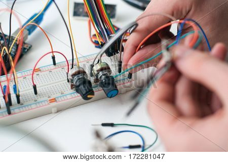 Hands connecting wires to breadboard closeup. Engineer constructing new gadget. Electronic development, diy, hobby, education concept