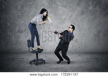 Picture of female leader standing on the chair while screaming to her male employee with a megaphone