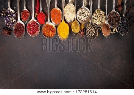 Various spices spoons on stone table. Top view with space for your text