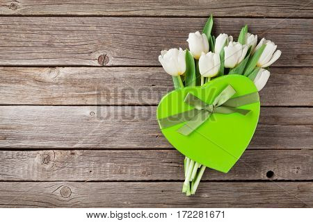 White tulips bouquet and heart shaped gift box on wooden background. Top view with space for your greetings