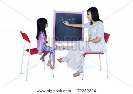 Portrait of young mother teaching alphabet to her little daughter on the blackboard isolated on white background