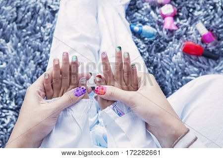 Close up of multicolored nail polish on beautiful finger of little daughter and young mother