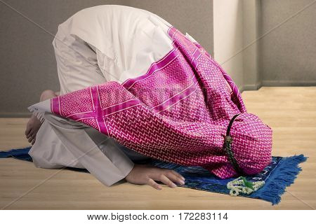Young Muslim male wearing Islamic clothes while posing prostration at home