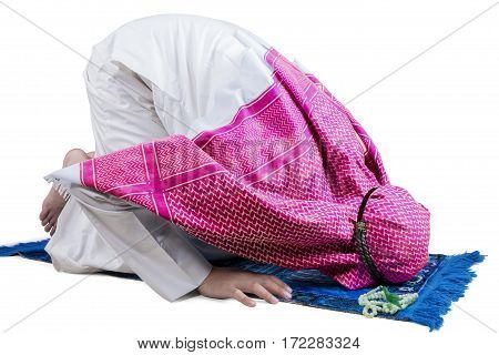 Young Muslim male wearing wearing Islamic clothes while posing prostration isolated on white background