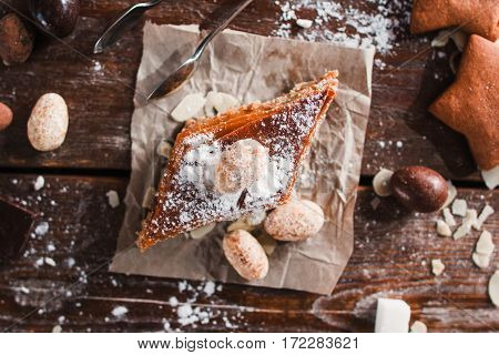 Sweet baklava with nuts on napkin flat lay. Top view on wooden table of baker with sweet ingredients and traditional turkish pastry. Confectionery, eastern dessert concept
