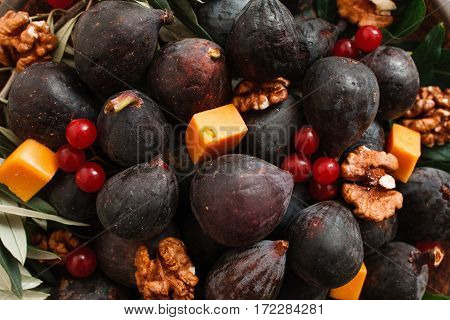Delicious snack of fig, cheese and nuts closeup. Food background of gourmet meal for wine, fresh fruits and walnuts. Gourmet, delicatessen, appetizer concept