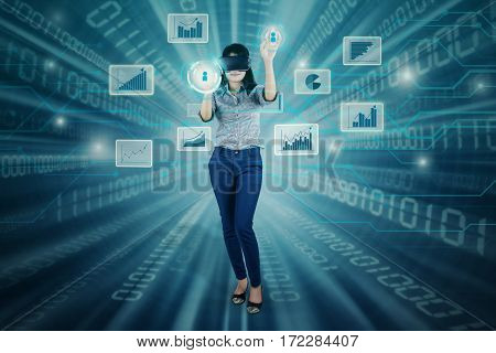 Successful businesswoman using virtual reality glasses while touching button screen and financial graph on the virtual screen