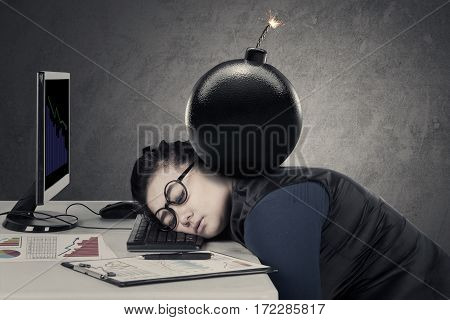 Young woman feeling tired with a bomb over her head while sleeping on the keyboard